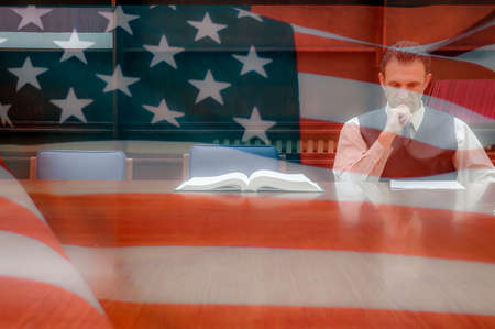 American lawyer reading contract in the office, united states of america flag background