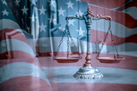 scales of justice on the table in the courtroom, united states flag background Imagens