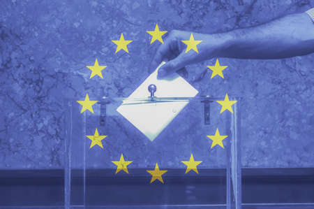 hand putting a blank ballot inside the box, european union flag background