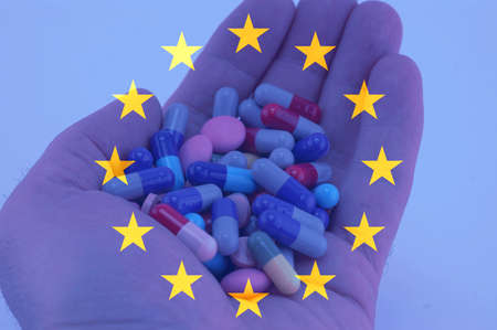 Hand holding multicolored pills, European union flag background Stock Photo