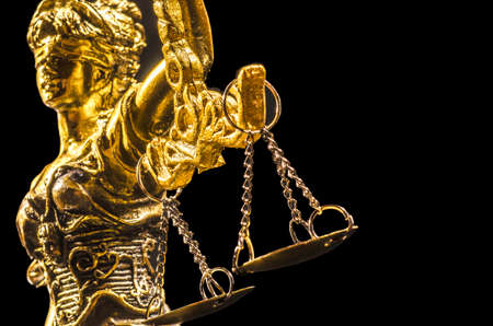 Golden Statue of lady Justice on the black background