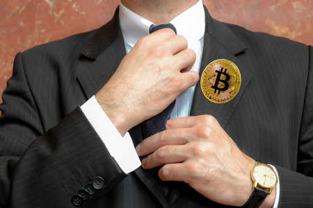 bitcoin badge on the lapel of businessman jacket Stock Photo