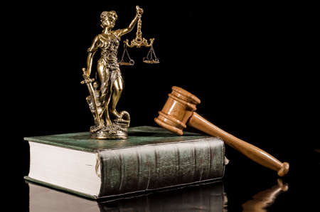 Statue of Justice on the book and wooden gavel on the black background