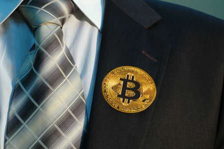 bitcoin badge on the lapel of businessman suit Stock Photo