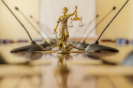 Statue of Lady Justice on the table with  microphones in th conference room