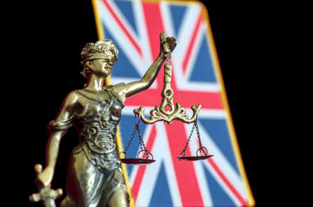 Statue of Lady Justice with  United Kingdom flag on the black background. Selective focus Stock Photo