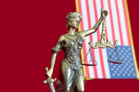 Statue of Lady Justice with  United States of America flag on the red background. Selective focus Stock Photo