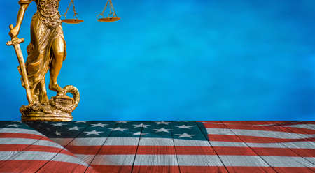 Statue of Justice and United States flag on the wooden floor with blue sky background Stock Photo