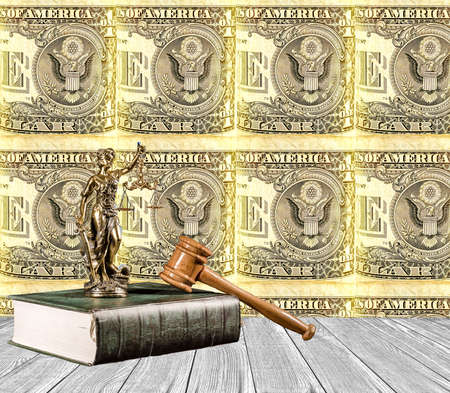 Justitia statues on the book with judicial hammer with a wooden floor and rolled up banknote of 1 US dollar as a background