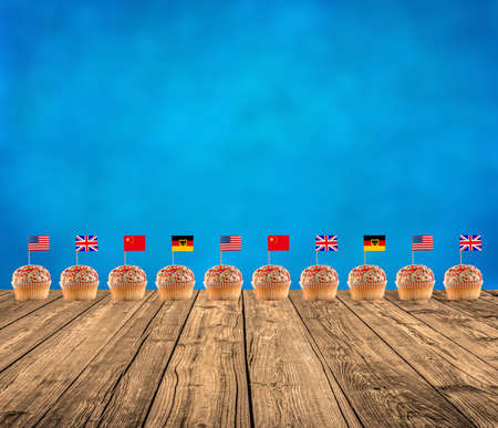 muffins with international flags on the wooden floor and blue sky background