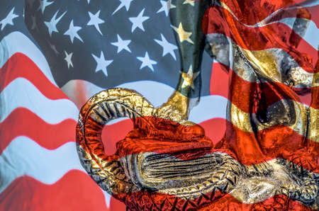 part of the statue of justice, the foot treads the head of the snake, the American flag of the background Stock Photo