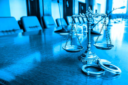 Scales of Justice and  handcuffs on the desk in courtroom,  blue tone