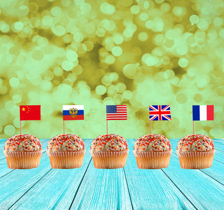 muffins with international flags on the wooden floor and green blurred background