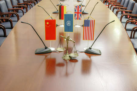 a decorative scale of justice at a conference table with international flags
