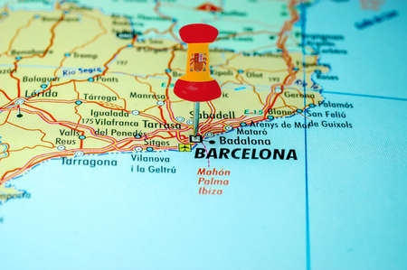 Push pin with spain flag stuck on a map centered on the city of Barcelona, Spain