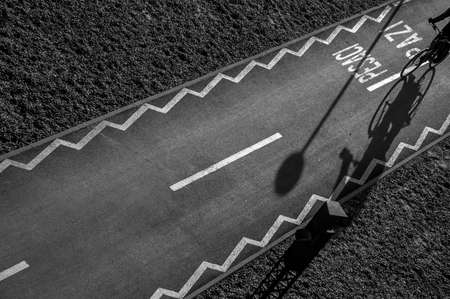 black and white photography of a cyclist on an asphalt track with shadows