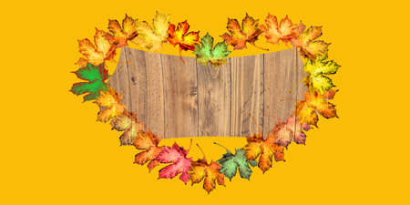 wood base with colorful autumn leaves in heart shape on a dark yellow background