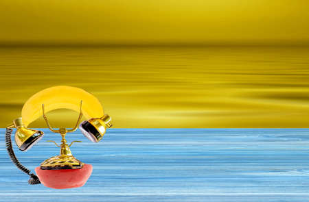 A fruit phone on a wooden dock with a golden sea in the background Stock Photo - 131724459