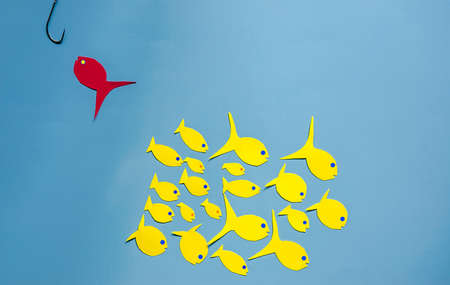 paper yellow and red fish on a blue background
