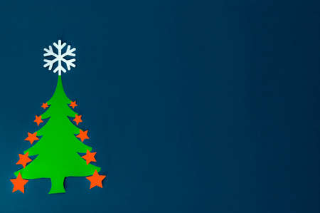 paper green Christmas Tree with snowflakes on a dark blue background Stock Photo