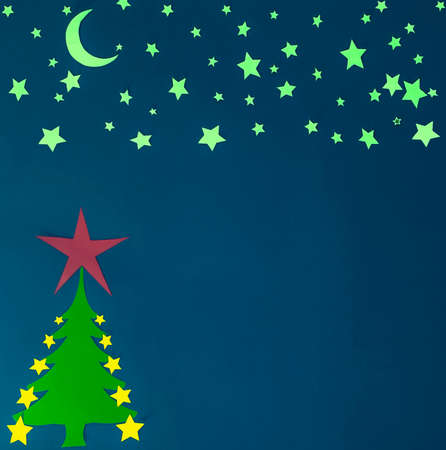 paper Christmas Tree with yellow moon and stars on a dark blue background