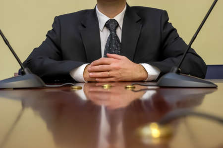 close-up of businessman at conference table with microphones