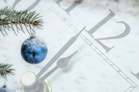 New Year Eve decoration: Blue meatlic Ball on a Christmas Tree, with a minute to midnight clock background.