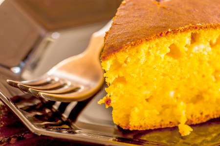 macro shot of cornbread with a fork on a black plate. selective focus