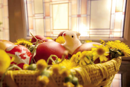 Decorated Easter eggs in basket with grass and dandelion Stock Photo