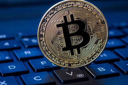 Golden bitcoin coin on laptop keyboard
