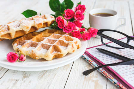 Pink roses, glasses, cup of coffee, notebook, pensil and Belgium waffles on wooden table. Autumn and winter, leisure concept.