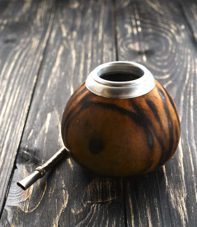 South American yerba mate tea in a wooden mate calabash at rustic table Stock Photo