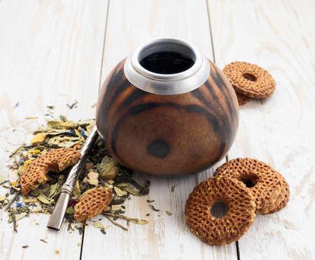 yerba mate: South American yerba mate tea in a wooden mate calabash and cookies at rustic table Foto de archivo
