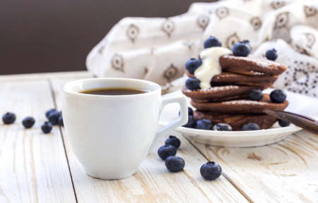 Hot coffee and buckwheat chocolate pancakes with blueberries and sour cream. Closeup. Breakfast Concept