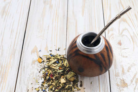 mate infusion: South American yerba mate tea in a wooden mate calabash at rustic table Stock Photo