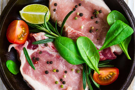 marinade: Pan of Fresh raw pork meat with pepper, lime, rosemary and spinach. Marinade. Ready ror cooking Stock Photo