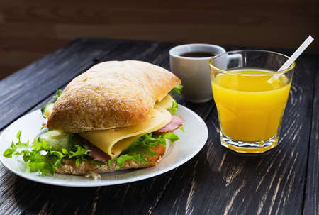 Chiabatta sandwich with ham, cheese, cucumber and lettuce, cup of coffee and orange juice for breakfast. Selective focus