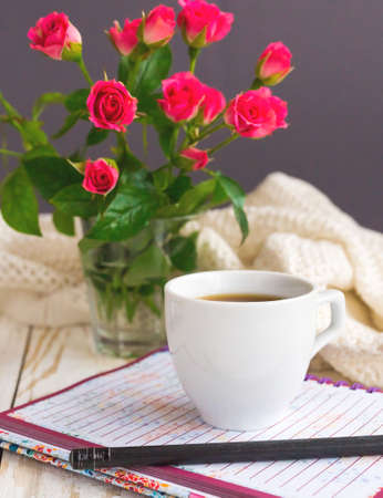 Warm knitted plaid, cup of coffee, notebook and pensil on wooden table. Bouquet of pink roses. Autumn and winter, leisure concept.