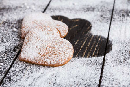Heart shaped ginger valentine cookies with  powdered sugar on a wooden table