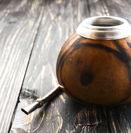 yerba mate: Sudamericano té de yerba mate en una calabaza compañero de madera en la mesa rústica Foto de archivo