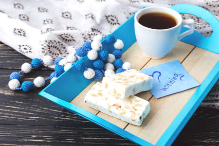 Egypt nougat with hazelnuts and cup of coffee in cosy blue tray. Breakfast consept