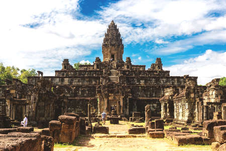 Temple in Angkor Wat Historical Complex, Siem Reap, Cambodia - December 6, 2016: Huge trees, galleries and walking tourists at sunny morning. Editorial