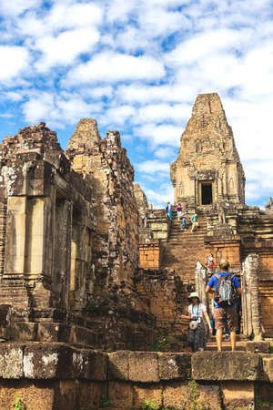 Pre Rup Temple, Siem Reap, Cambodia - December 5, 2016: Towers and galleries and walking tourists at sunny morning.