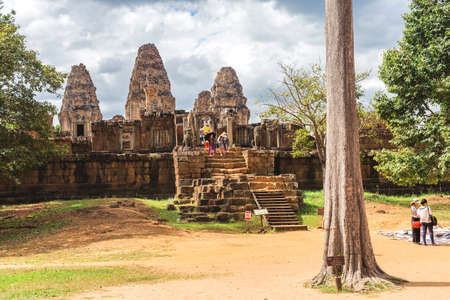 Temple in Angkor Wat Historical Complex, Siem Reap, Cambodia - December 5, 2016: Huge trees, galleries and walking tourists at sunny morning.