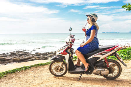 Koh Lanta Island, Krabi Province, Thailand - December 10, 2016: touristic blond Girl with smoothie sitting at Honda motobike on the observation point near exotic beach