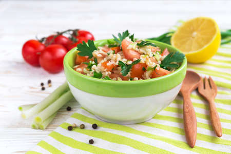 green onions: Green salad with sliced tomatoes, spinach, bulgur, green onions, parsley and lemon on wooden table. Healthy food and vegetarian concept Stock Photo