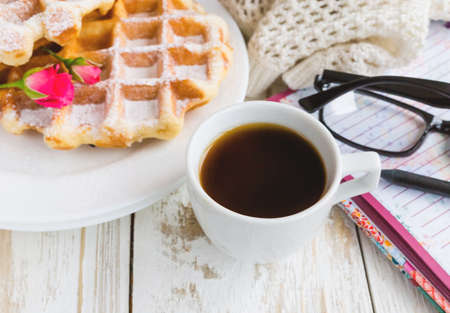 Warm knitted plaid, glasses, cup of coffee, notebook, pensil and Belgium waffles on wooden table. Autumn and winter, leisure concept. Stock Photo