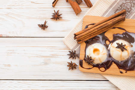 Classic italian homemade dessert panna cotta with chocolate, anise and cinnamon spices on wooden table. Stock Photo