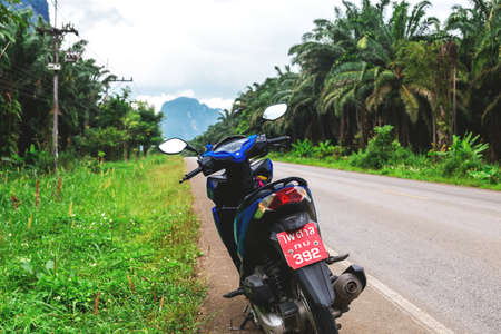 motobike: Krabi Province, Thailand - December 15, 2016: Honda motobike at asphalt road though the tropical jungle, rainforest