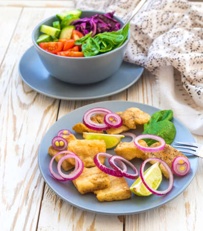 Crispy fried fish tilapia with lime and onion; and green vegetable salad. Selective focus. Closeup
